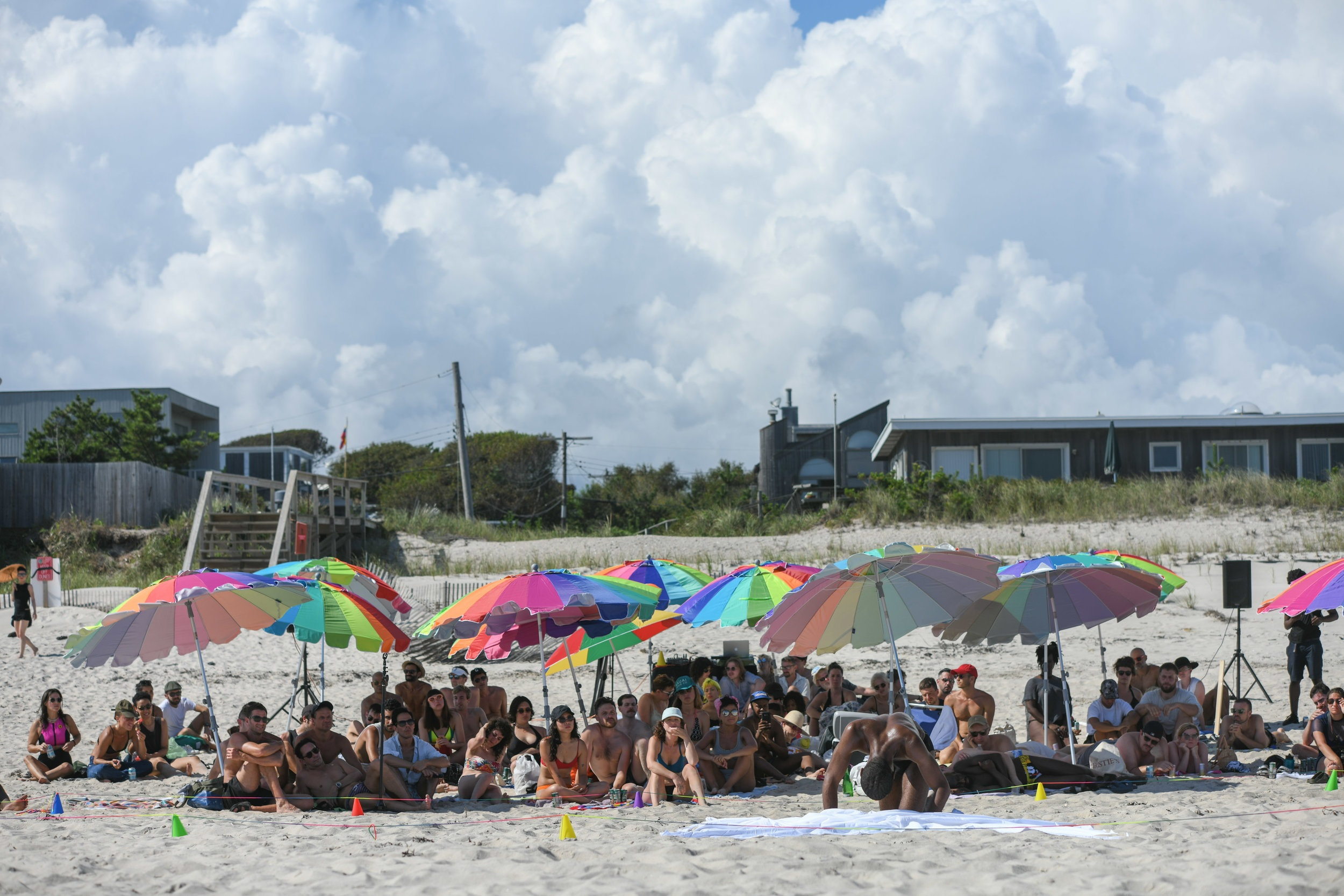 I crawl toward the camera, digging my hands and knees into the sand, as the crowd watches under an arrangement of colorful beach umbrellas. Photo by Nir Arieli