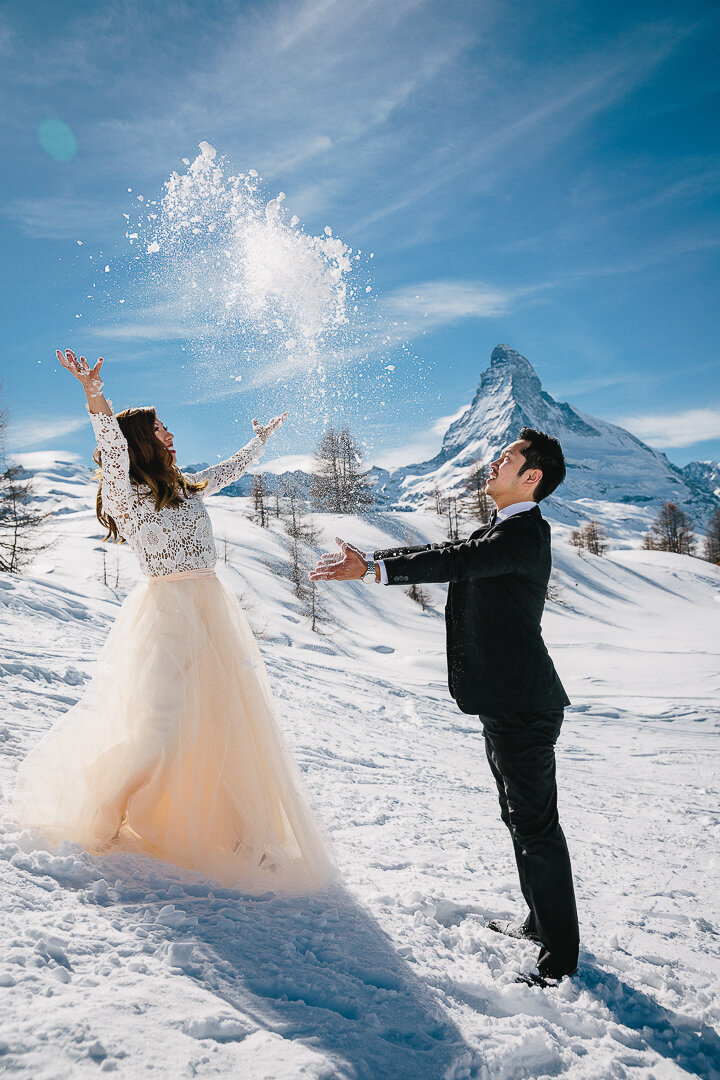 A couple enjoy a moment of pure joy in the snow in Zermatt while taking pictures for their engagment shoot