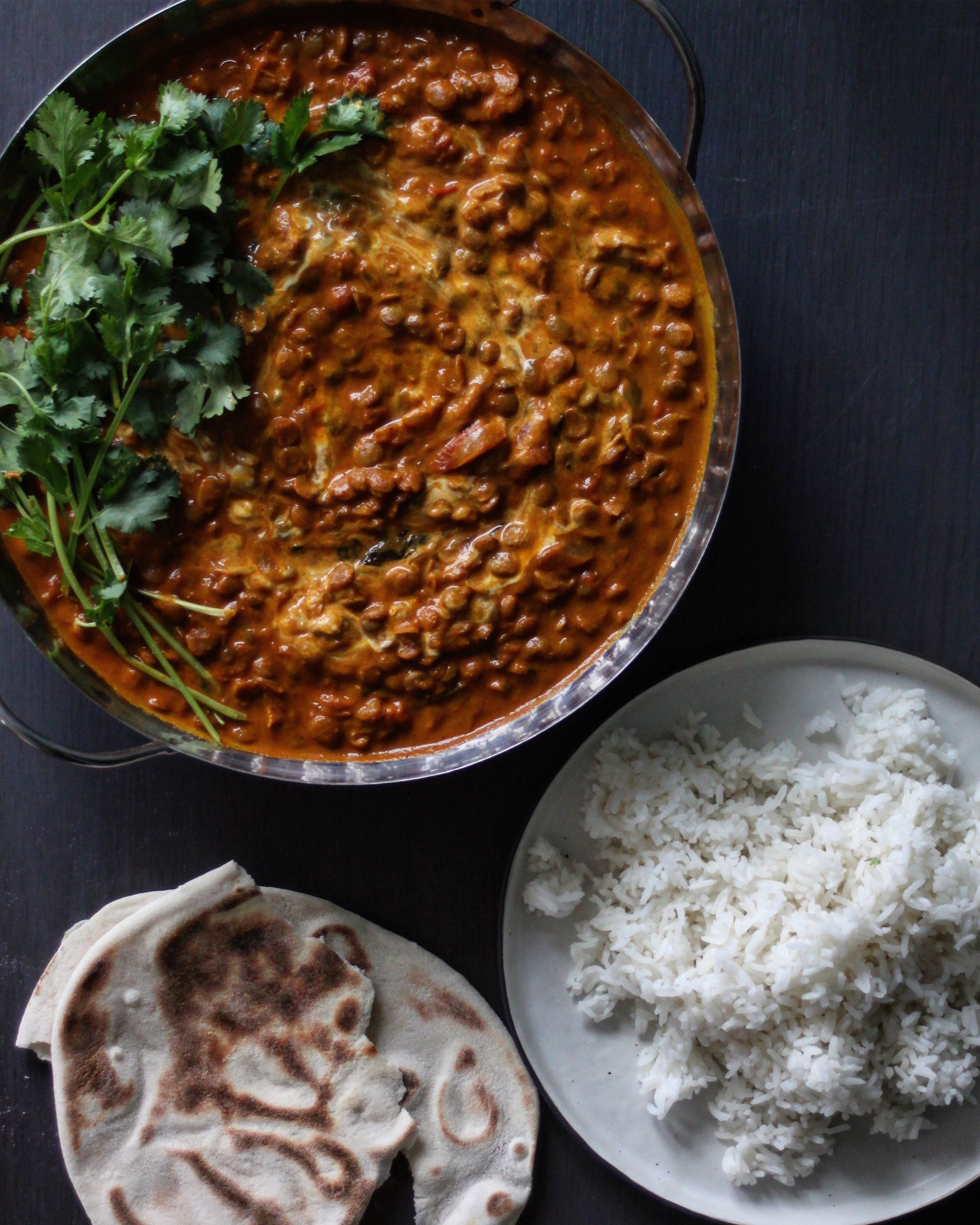 Ingredients    1 Large Onion  2 Cloves Garlic  1 Birdseye Chili  1tsp Grated Ginger (Heaped)  1tbsp Turmeric  1tsp Ground Cumin (Heaped)  1tsp Paprika (Heaped)  2tsp Garam Masala  2 400g Tins Chopped Tomatoes  400g Tin Coconut Milk  1 Cup Green Lentils  2tsp Tomato Puree  50g Fresh Spinach    Method    Chop the onion finely and place into a large frying pan/saucepan with a drizzle of vegetable oil and a pinch of salt and pepper. Cook on a medium heat for a minute or two until soft. Chop the chili finely, crush the garlic, grate the ginger and add them all to the softened onions. Cook for another 5 minutes.  Next add the spices to the pan. Stir to combine and allow the spices to cook for a minute until the aromas begin to fill the kitchen. Now add the tomatoes - fill the two empty tins with water and add these to the pan too along with the tomato puree. Stir all the ingredients to combine.  Now add the lentils and coconut milk. Bring the mix to a boil and reduce to a simmer for 45 minutes or until the lentils are soft and cooked through. Finish the curry with the spinach five minutes before it is ready to serve, just so that the leaves begin to wilt.  Serve the curry with steamed rice, flatbreads and a swirl of natural yogurt.