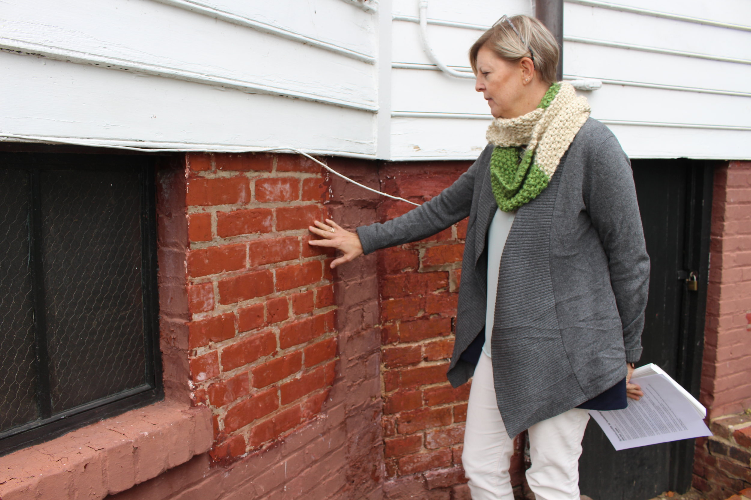 Preservation Director Amy Swartz indicates a test patch on the foundation.