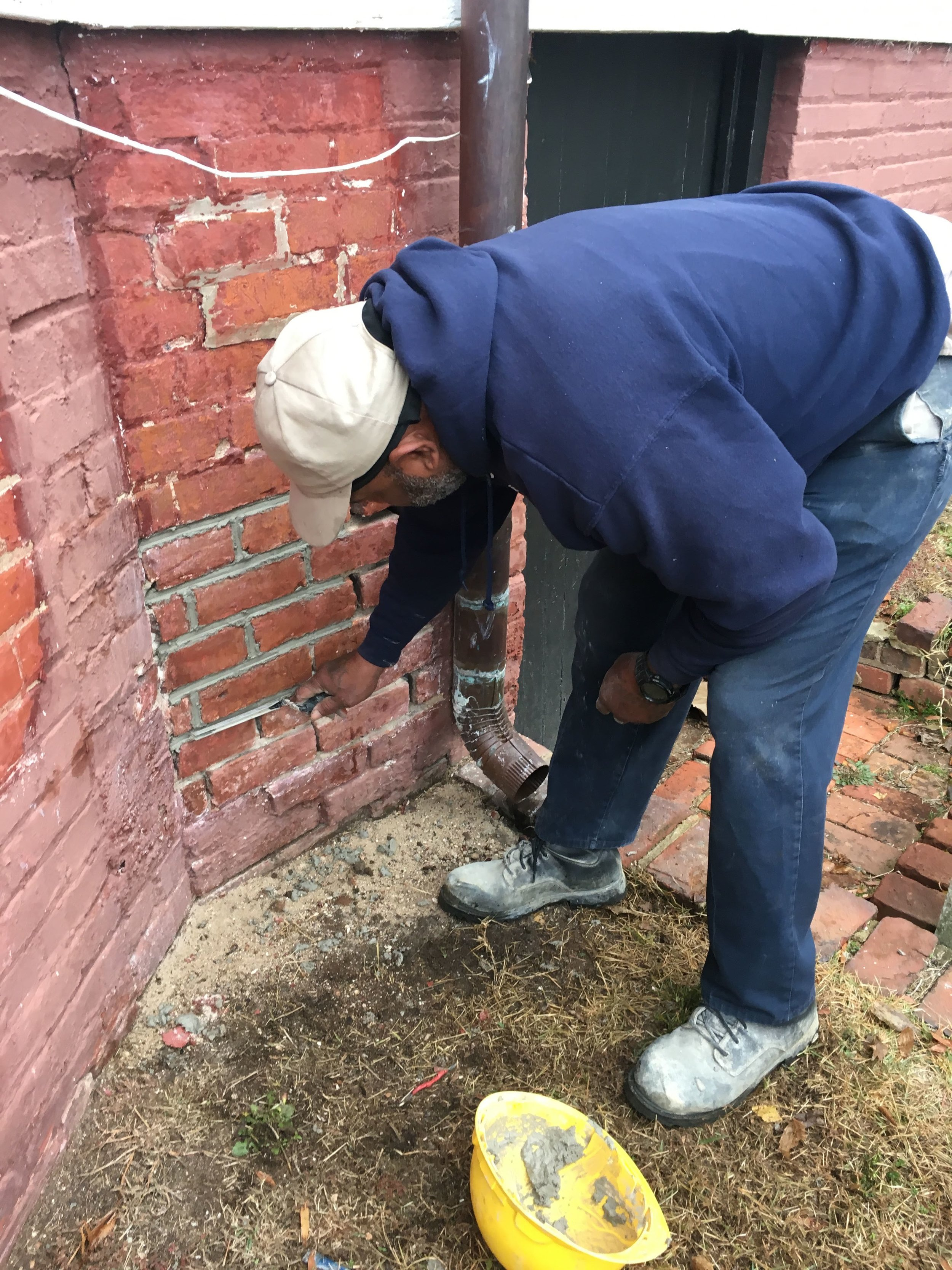 The red paint must be removed and the brick foundation repaired and repointed.