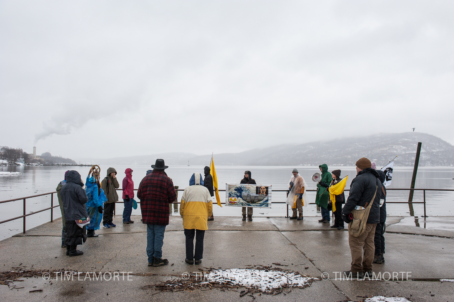 Maria Maybee leads a water ceremony at Peekskill Landing Park, north of Indian Point's two domed reactors to the left.