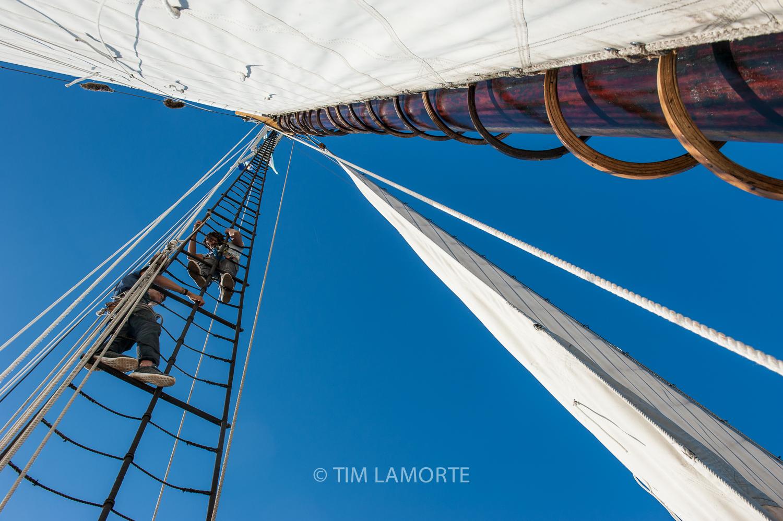 Crew member Manni Portes helps photographer Al Thompson climb the rigging.