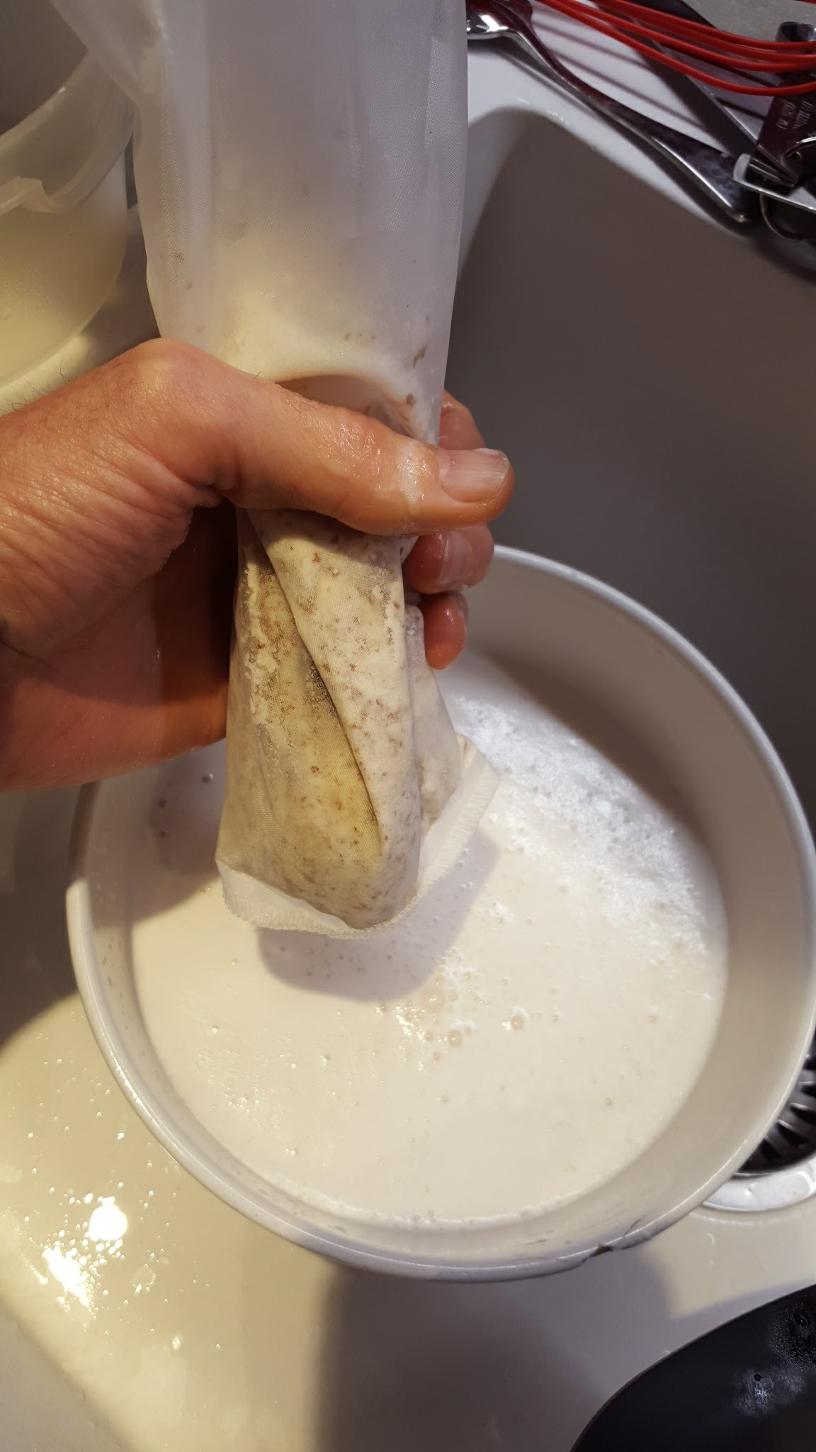 Squeeze the remaining almond milk out of the nut milk bag.