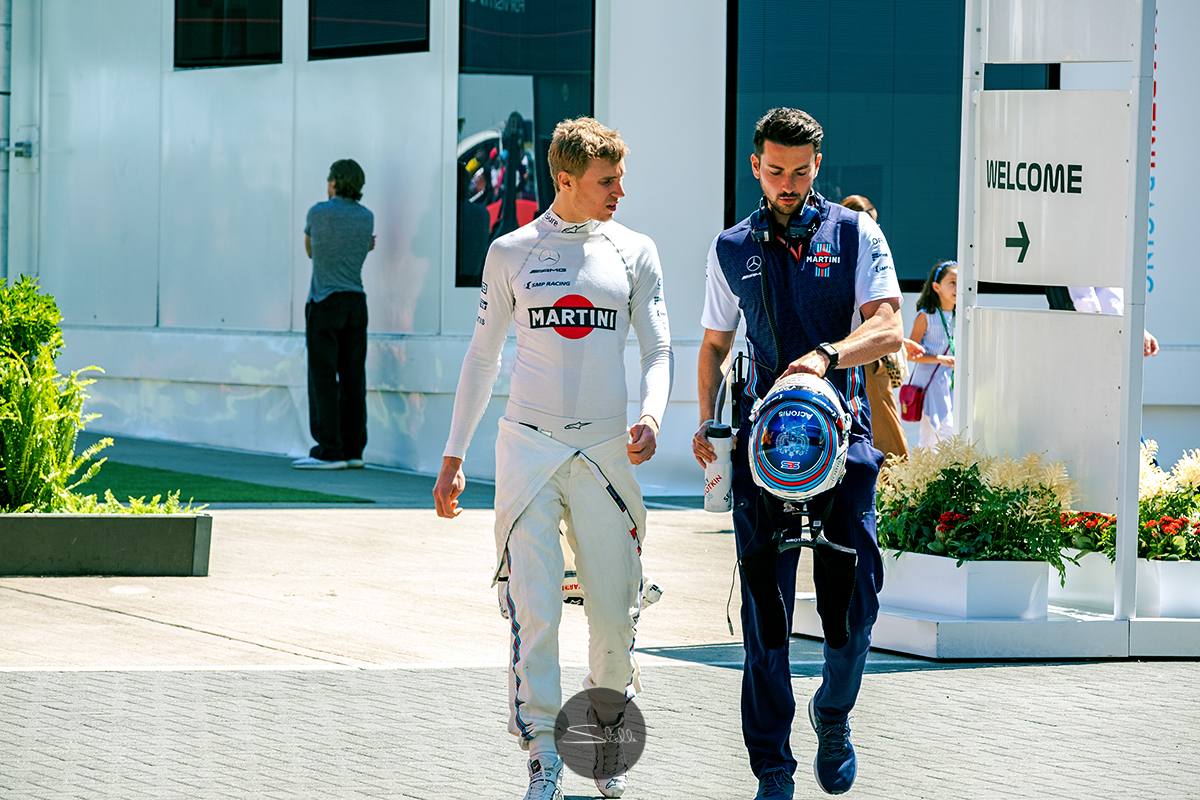 Sergey and his trainer, Tom, walk from the motorhome to the garage ahead of a session