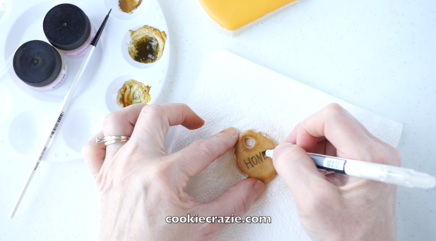 Using a  black food color marker,  add words, dots, lines, and/or embellishments to the tag.