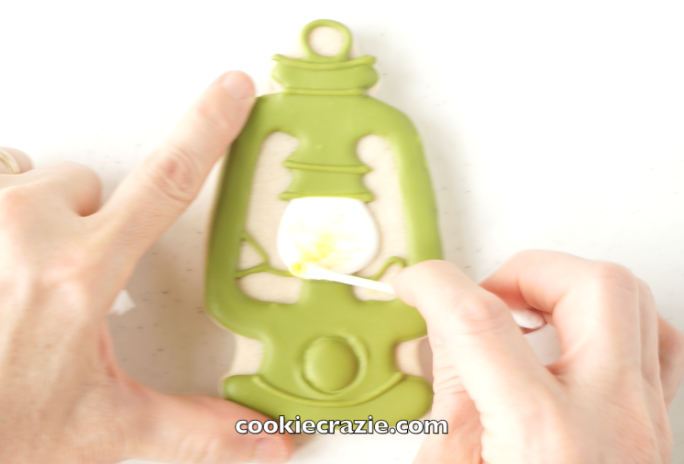 """Allow the cookie to dry overnight. Using a cotton swab, spread dry yellow luster dust within the """"bulb"""" of the lantern to give it a lighted effect. (Dust found  HERE )"""