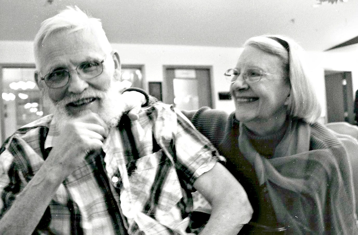 Two seniors smile in a black and white photo