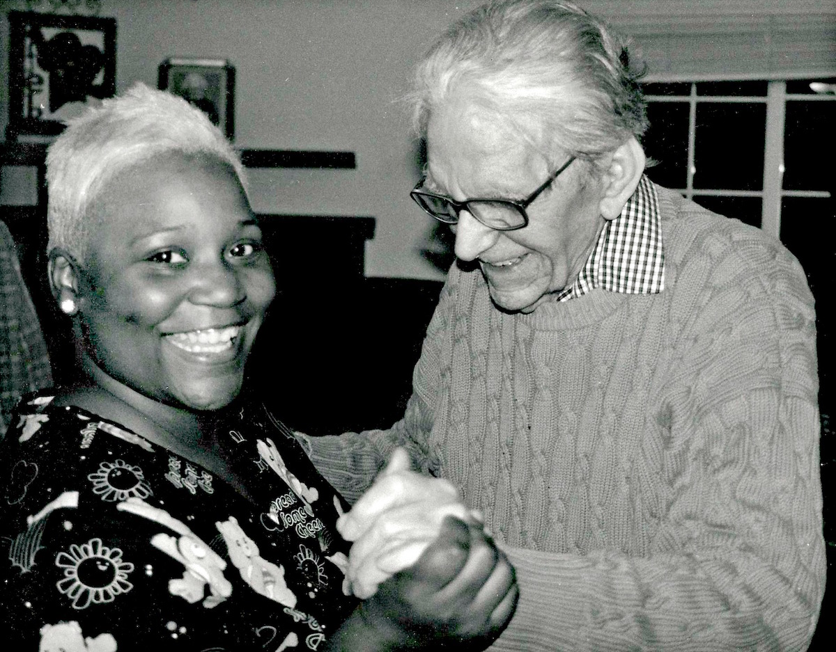 care giver and male senior resident dance