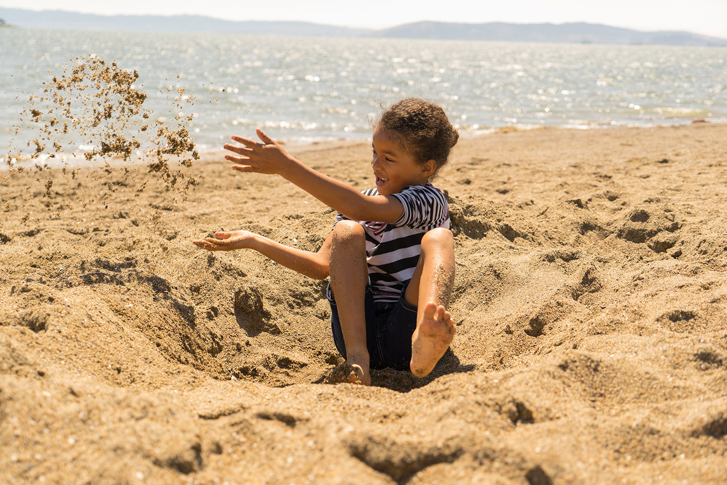 girl digging at Alameda beach-SF Bay area lifestyle photographer