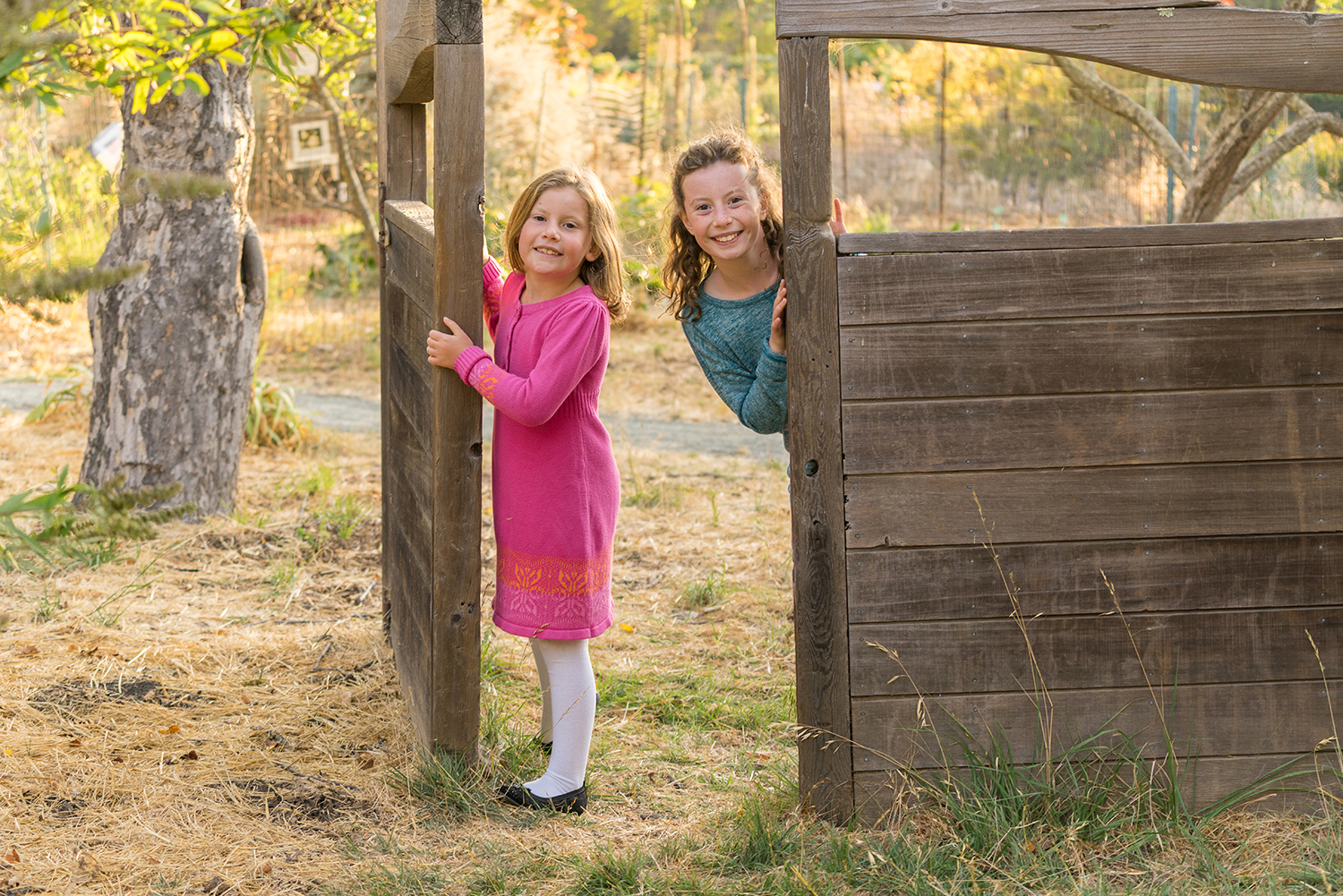 two sisters peering through the gate at Crow Canyon Gardens-San Ramon photographer