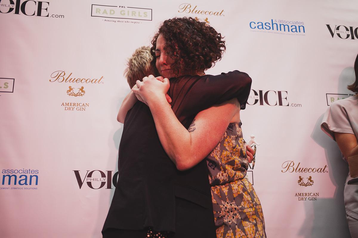Educator of The Year Eileen R. Heisman hugs presenter Lansie Sylvia at The Rad Awards. April 18. 2015. The Dreaming Building. Chris Fascenelli/Rad-Girls.com.