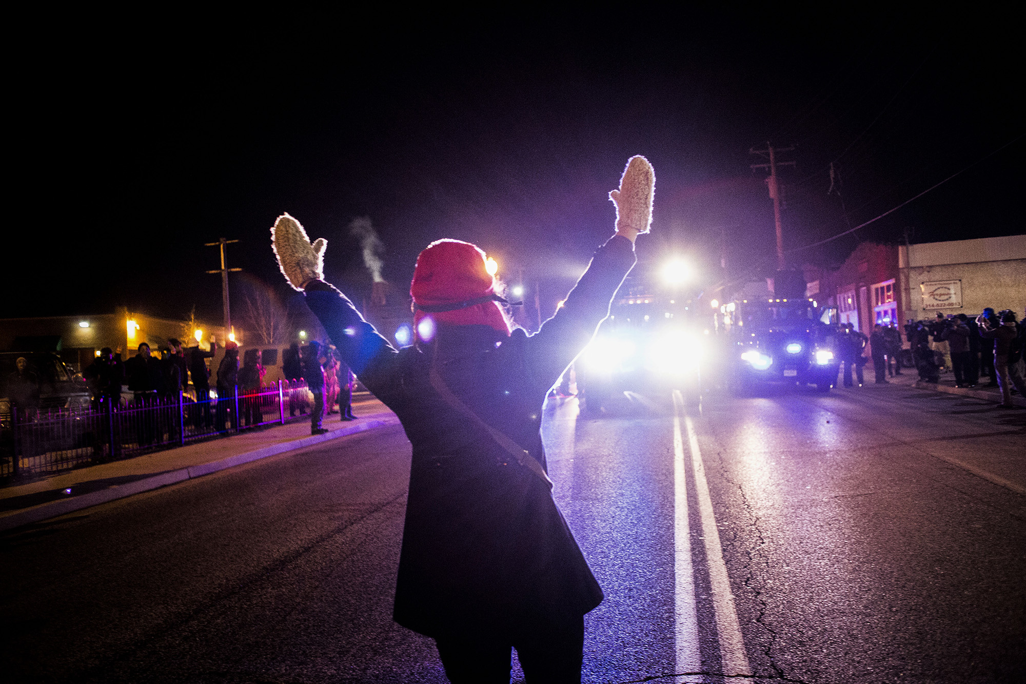 "A protester stands in front of authorities saying ""hands up, don't shoot"" on Nov. 25, 2014 in Ferguson, MO."