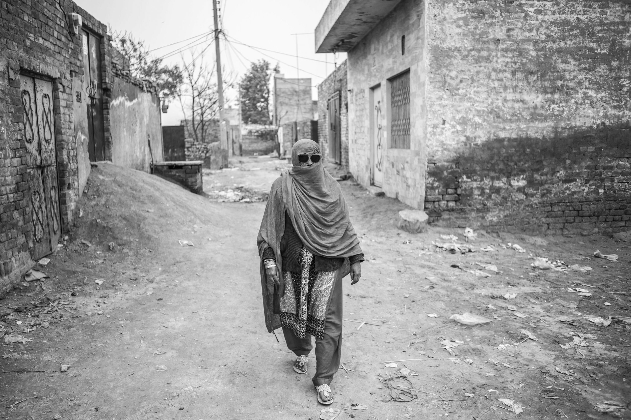 Sarwari Bibi, covers her face when she leaves her residence on Jan. 23, 2016 in Lahore, Pakistan.