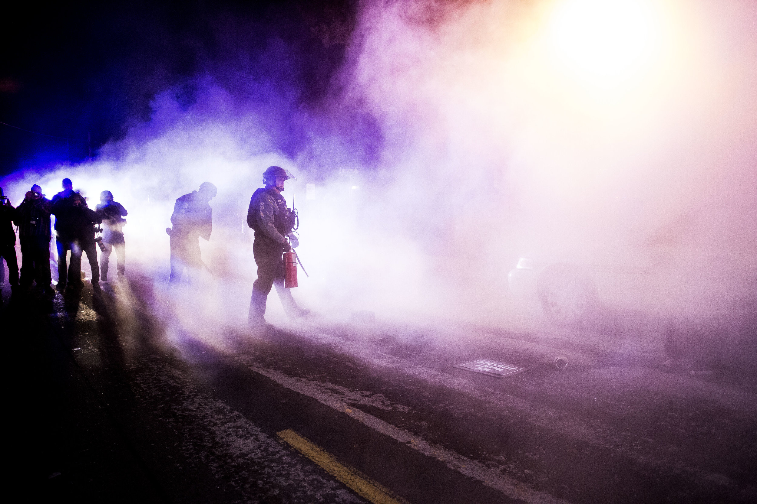 A police official puts out a fire set to a police vehicle outside the Ferguson City Hall on Nov. 25, 2014, in Ferguson, MO.