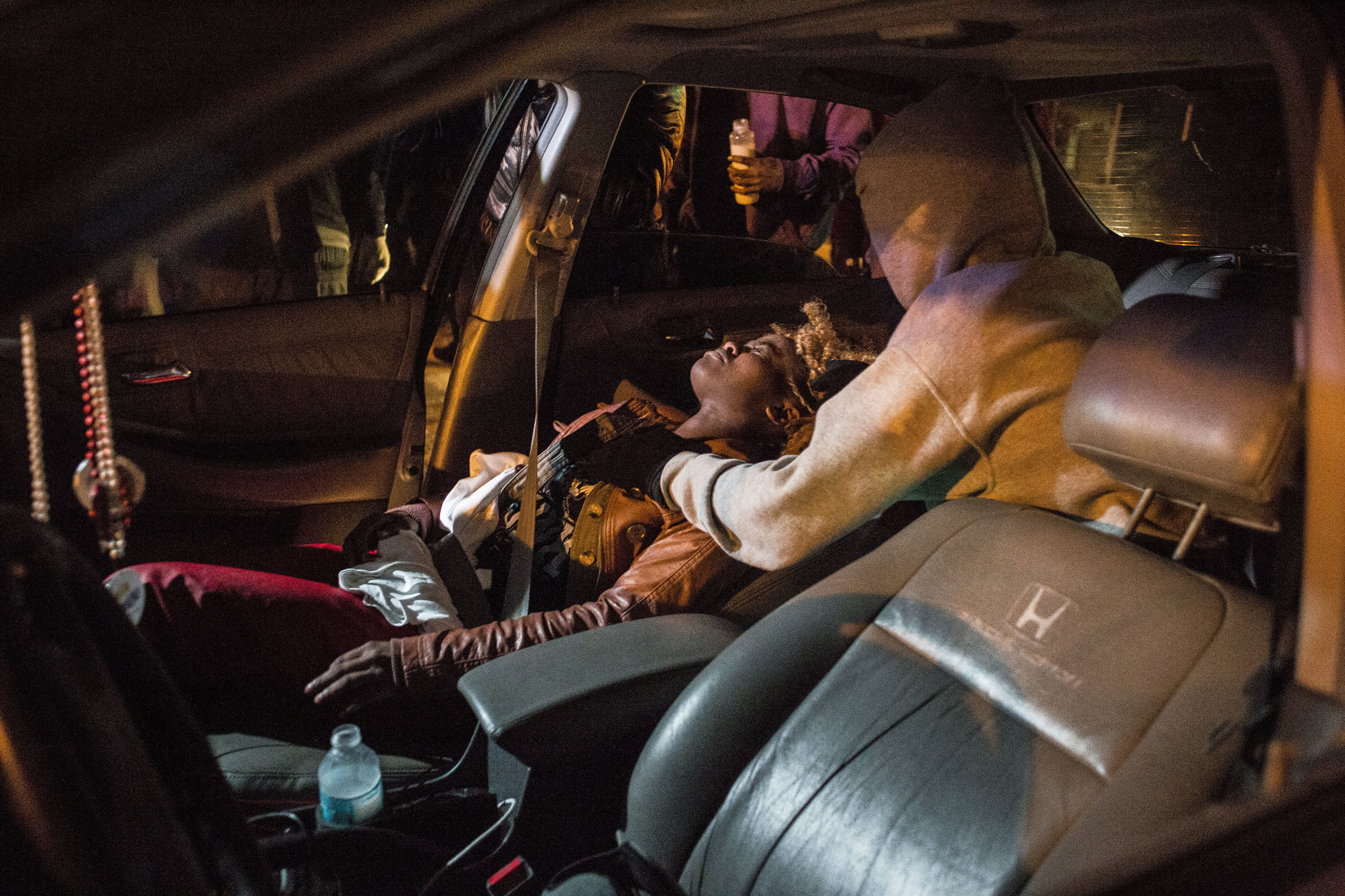 A protester lays in a car after police sprayed her with tear gas on Nov. 24, 2014 in Ferguson, MO.
