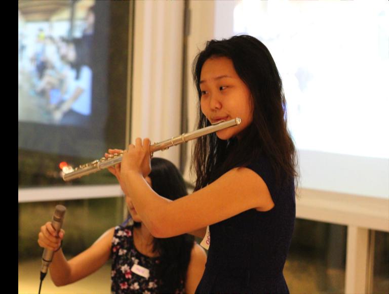 TASSEL volunteer Jeniffer performing on the flute.