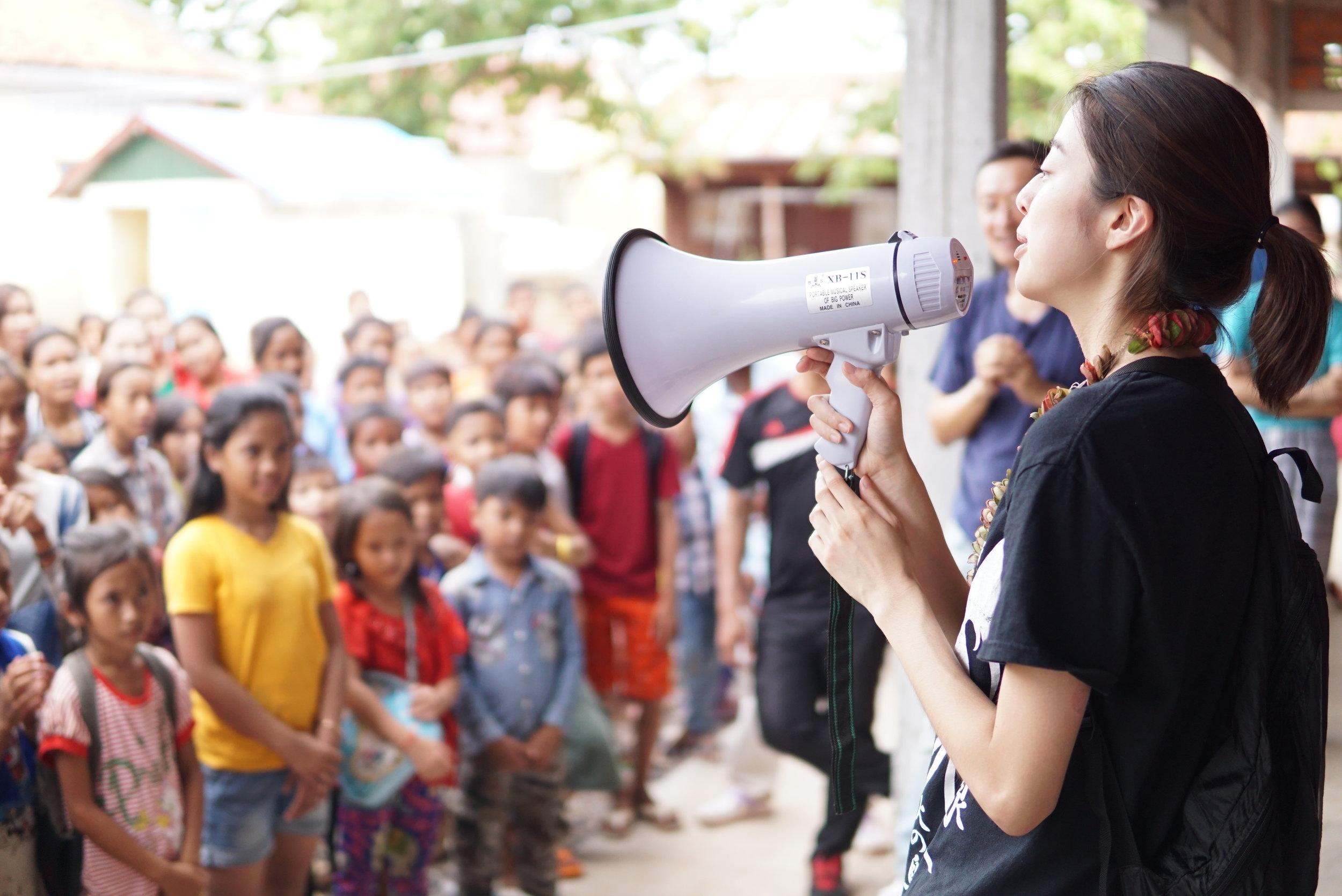 Miyu introducing herself before the students of the Samrang TASSEL School, 2016.