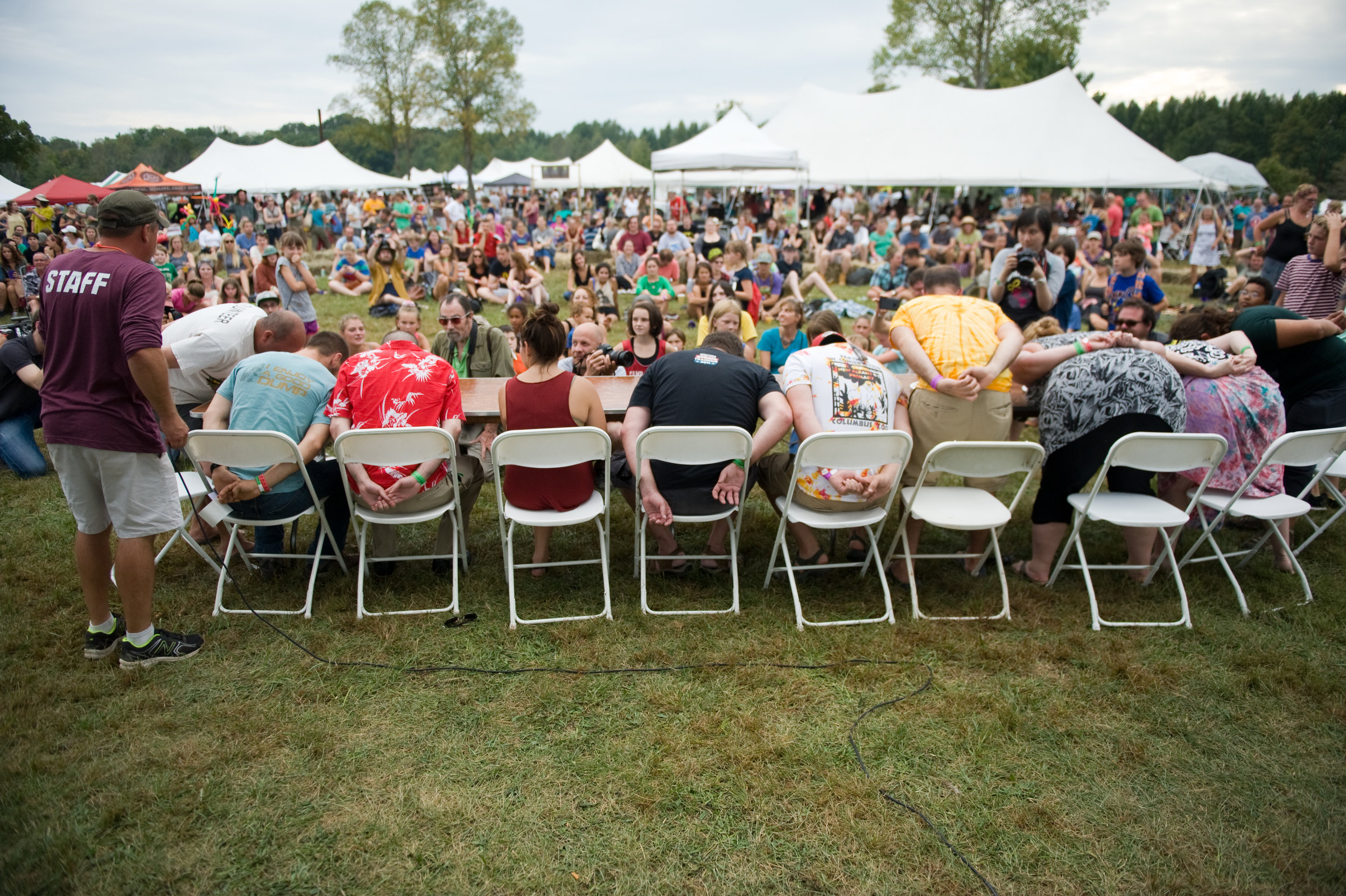 Festival attendees participating in a pawpaw eating contest, as the other fest goers cheer them on. Photo by  Michelle Waters
