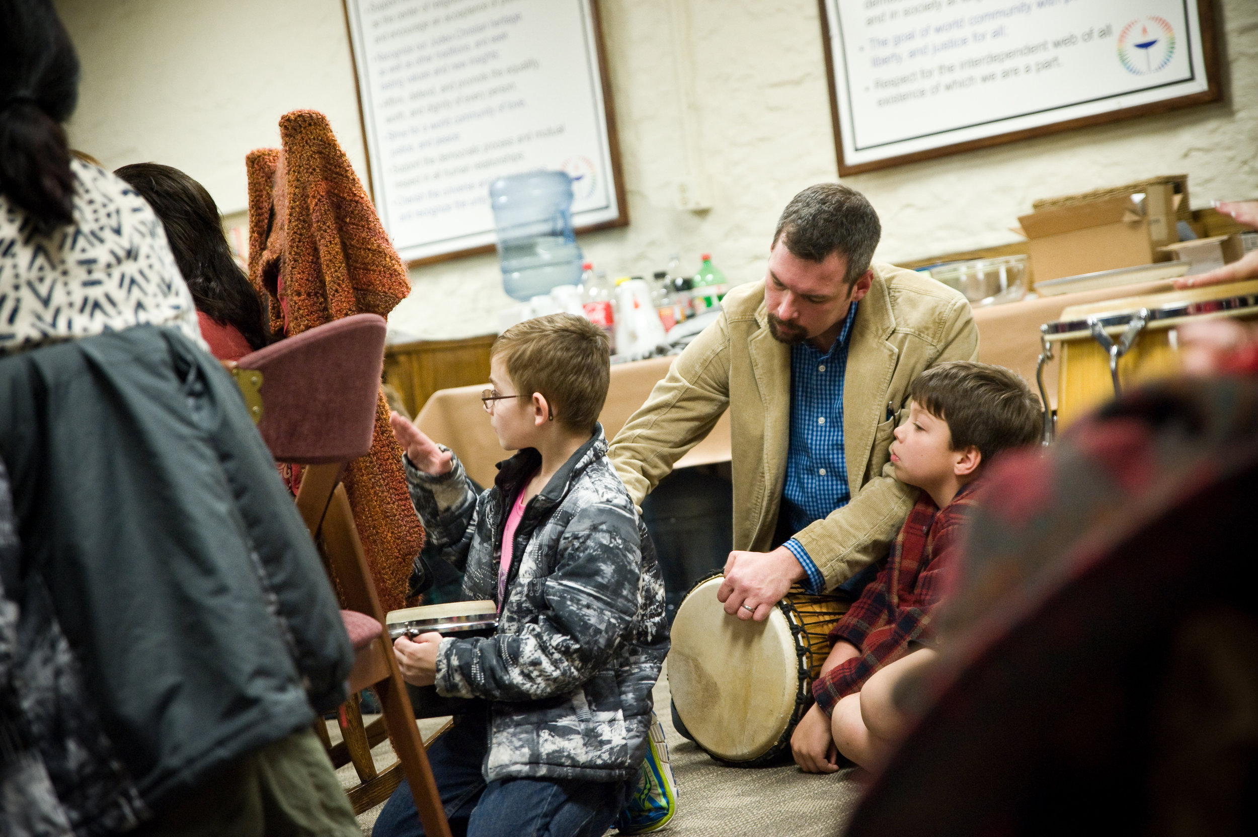Aaron Whited and his son are sitting in on the drum circle. Aaron led an open mic earlier in the evening, and also helped coordinate the candlelight ceremony, following the circle. Photo by Michelle Waters.