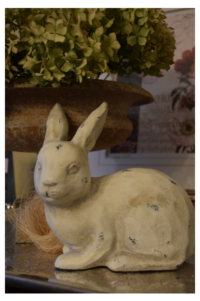 I made a little spring display on a silver tray with this cute rabbit, straw nest, and aged metal urn filled with dried green hydrangeas.  A large botanical print was used as the background.