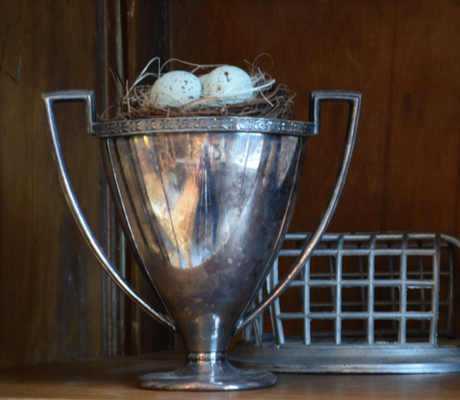 Silver trophy cup with bird's nest and antique flower frog add a sense of history to this antique hutch shelf.