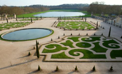 Arabesque parterre gardens symmetrically placed around the the circular water feature.