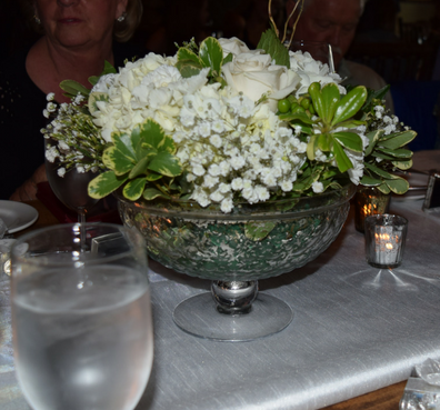 The flower arrangements in raised silver glass pedestals.