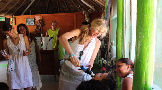 Marla giving child clean water at Life Source Retreats Distribution at Dos Palmas August 11 2016.JPG