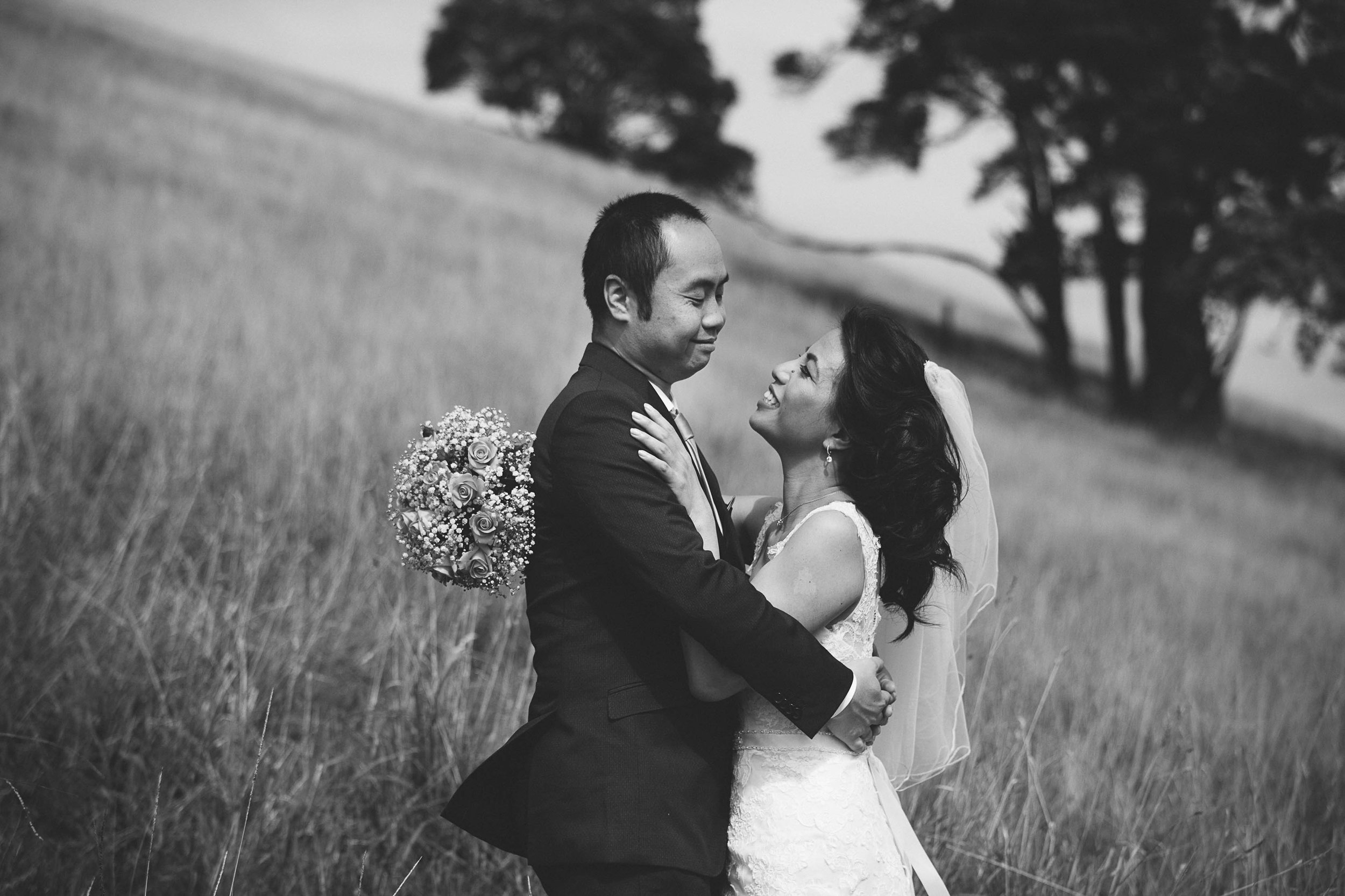 Wedding photography - black & white photo of couple hugging in field