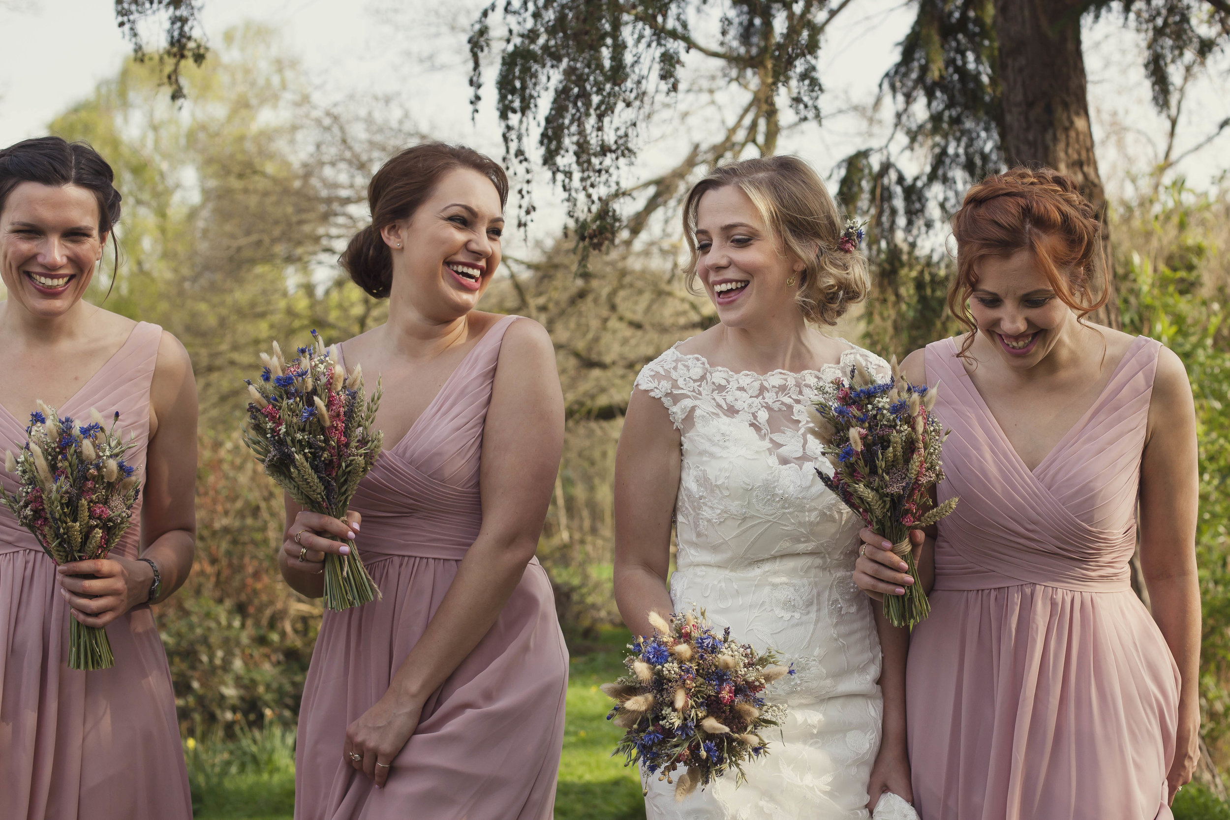 Bride and bridesmaids laughing in wedding photo