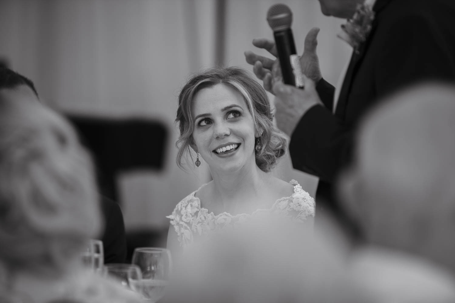 Smiling bride during speeches at wedding ceremony
