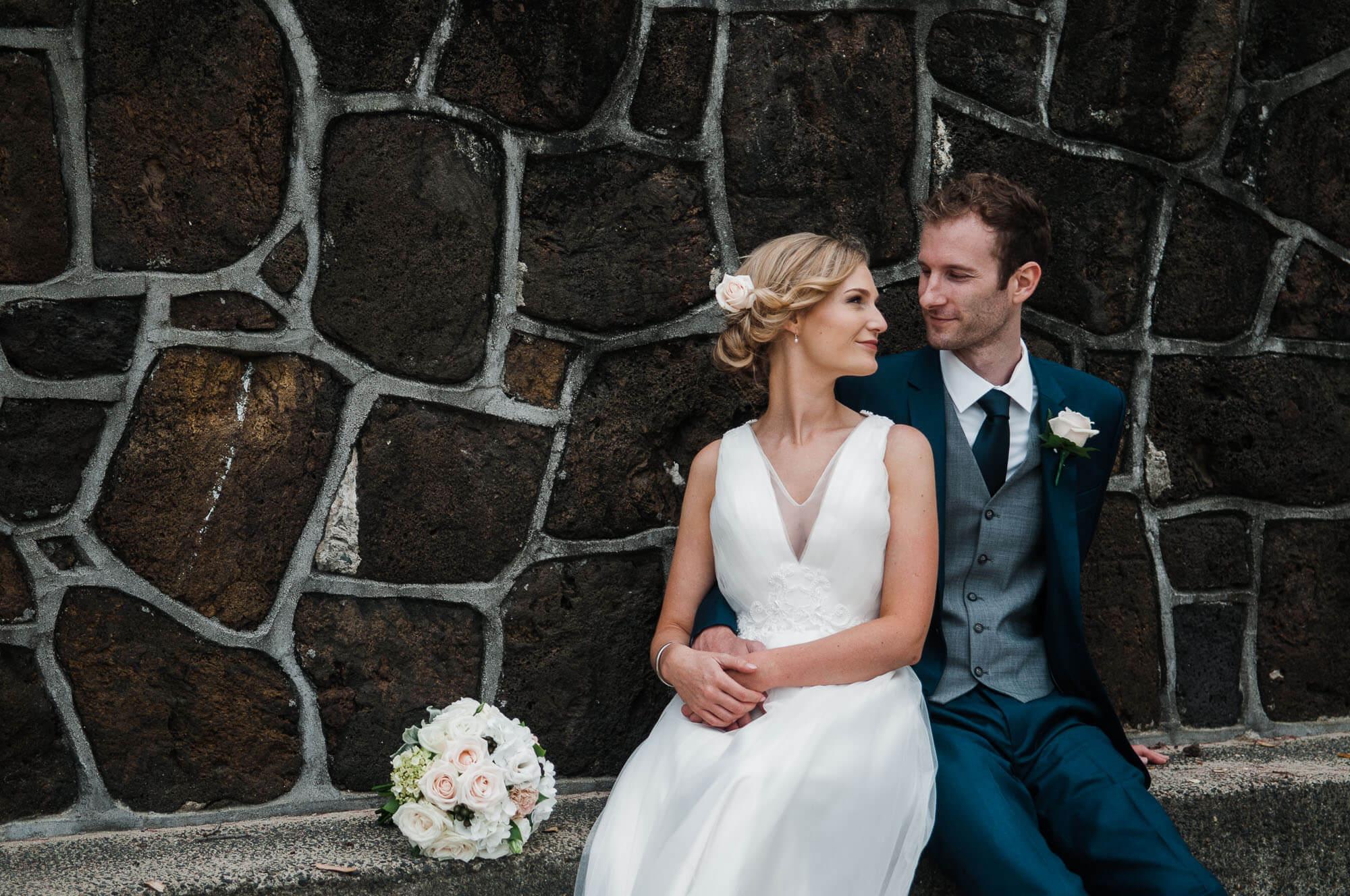 bride-and-groom-sitting-on-wall.jpg