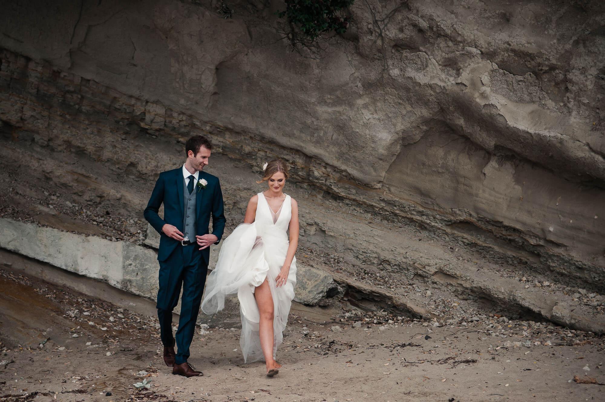 bride-and-groom-walk-barefoot-down-beach.jpg