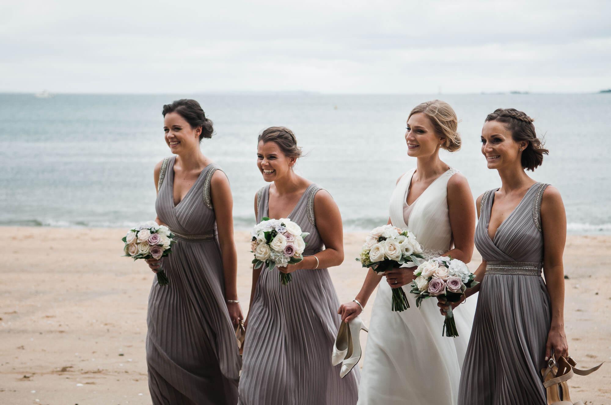 bride-walks-down-beach-with-bridesmaids.jpg
