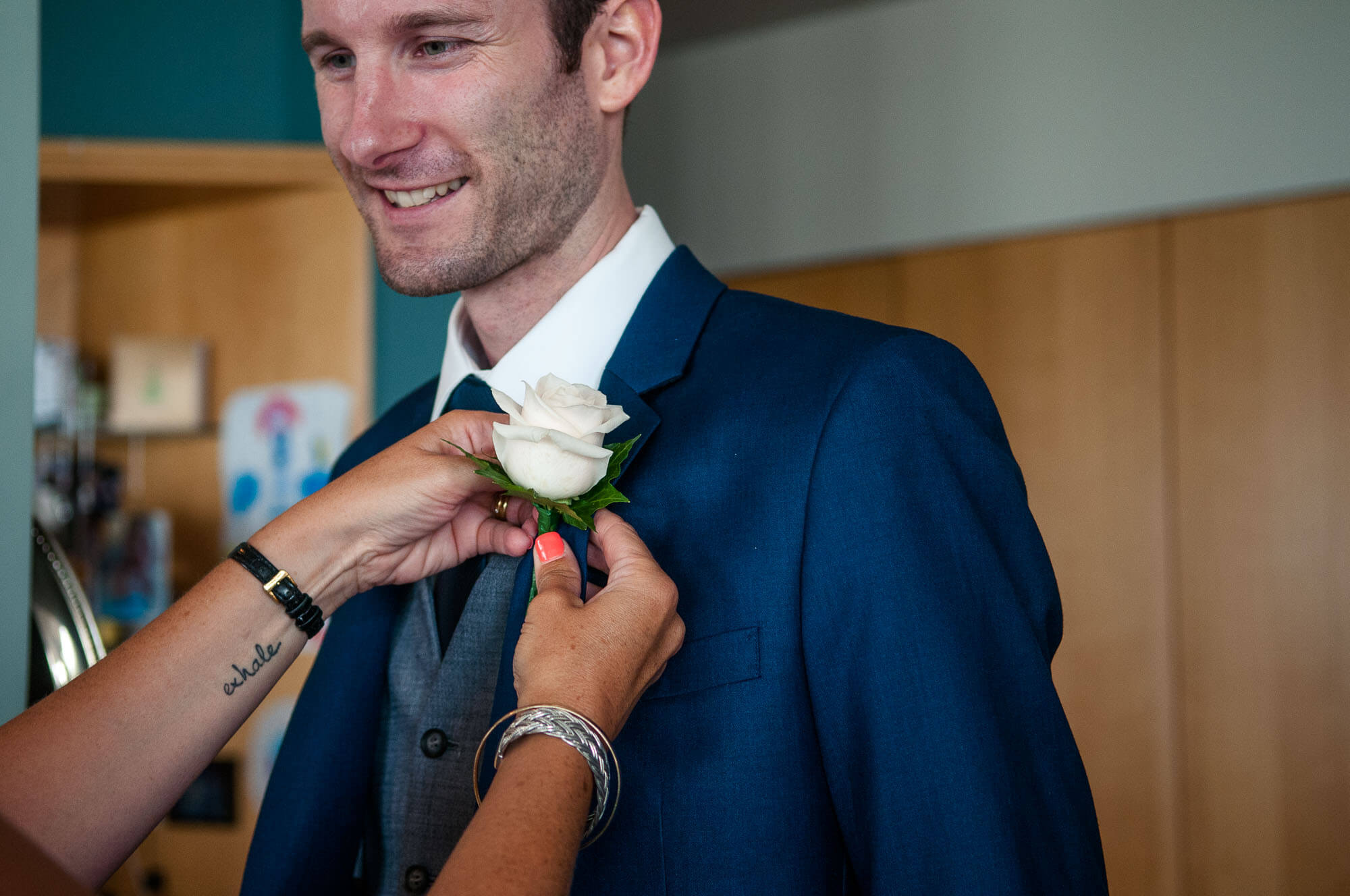 lady-with-tattoo-adjusts-grooms-buttonhole.jpg