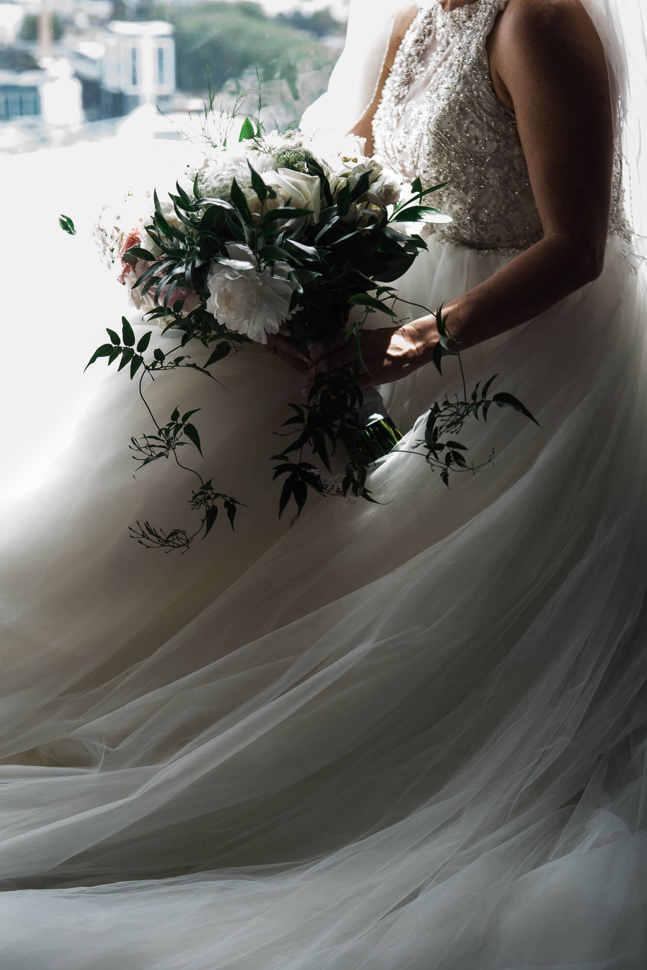bride-sitting-in-window-with-bouquet.jpg