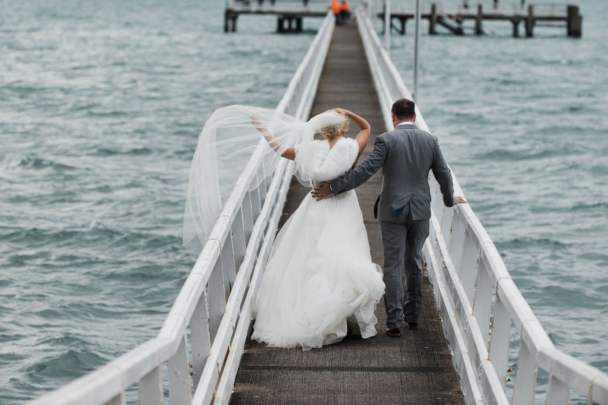 bride-and-groom-walk-down-pier.jpg