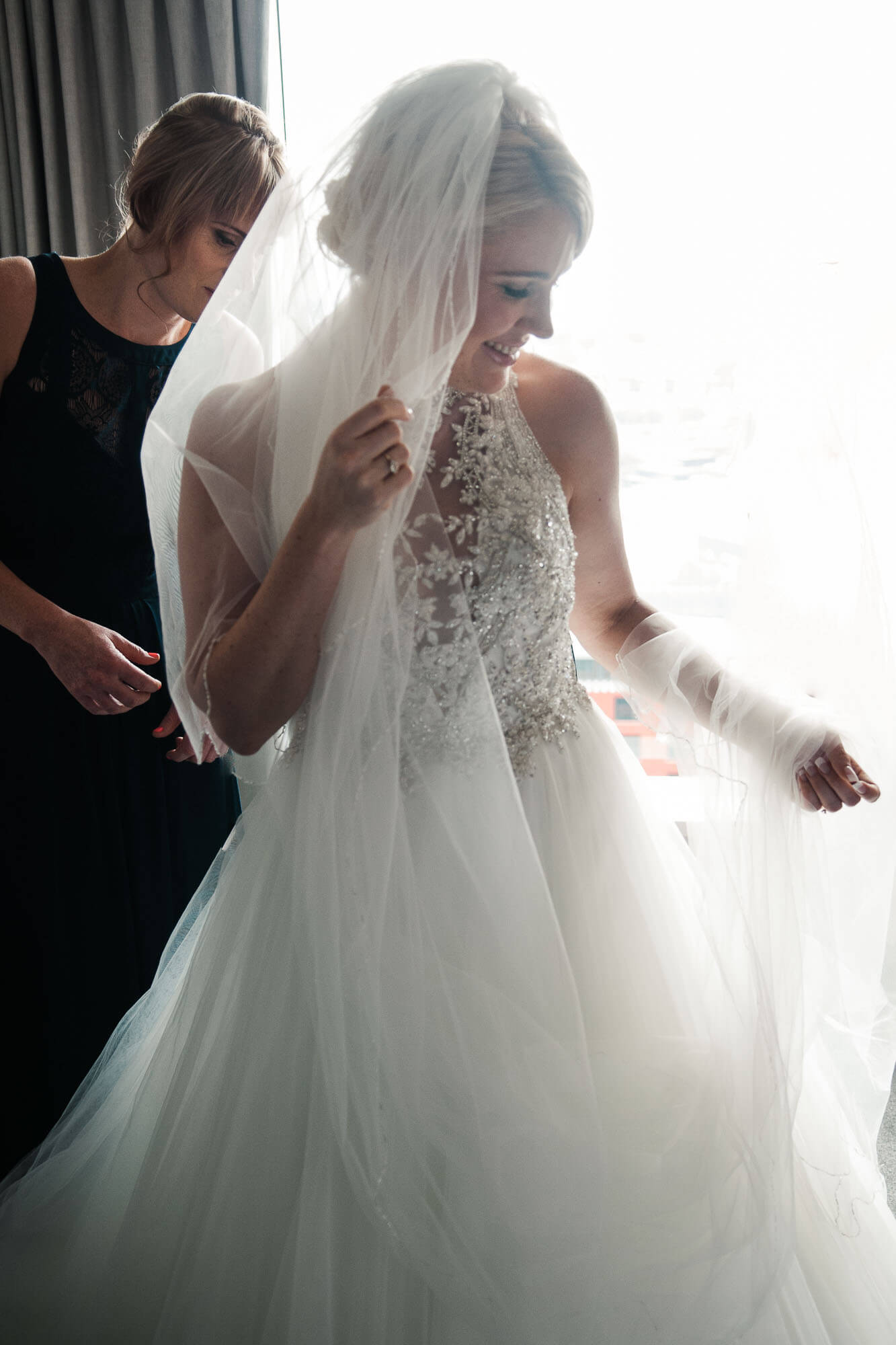 bride-getting-dressed-with-veil.jpg