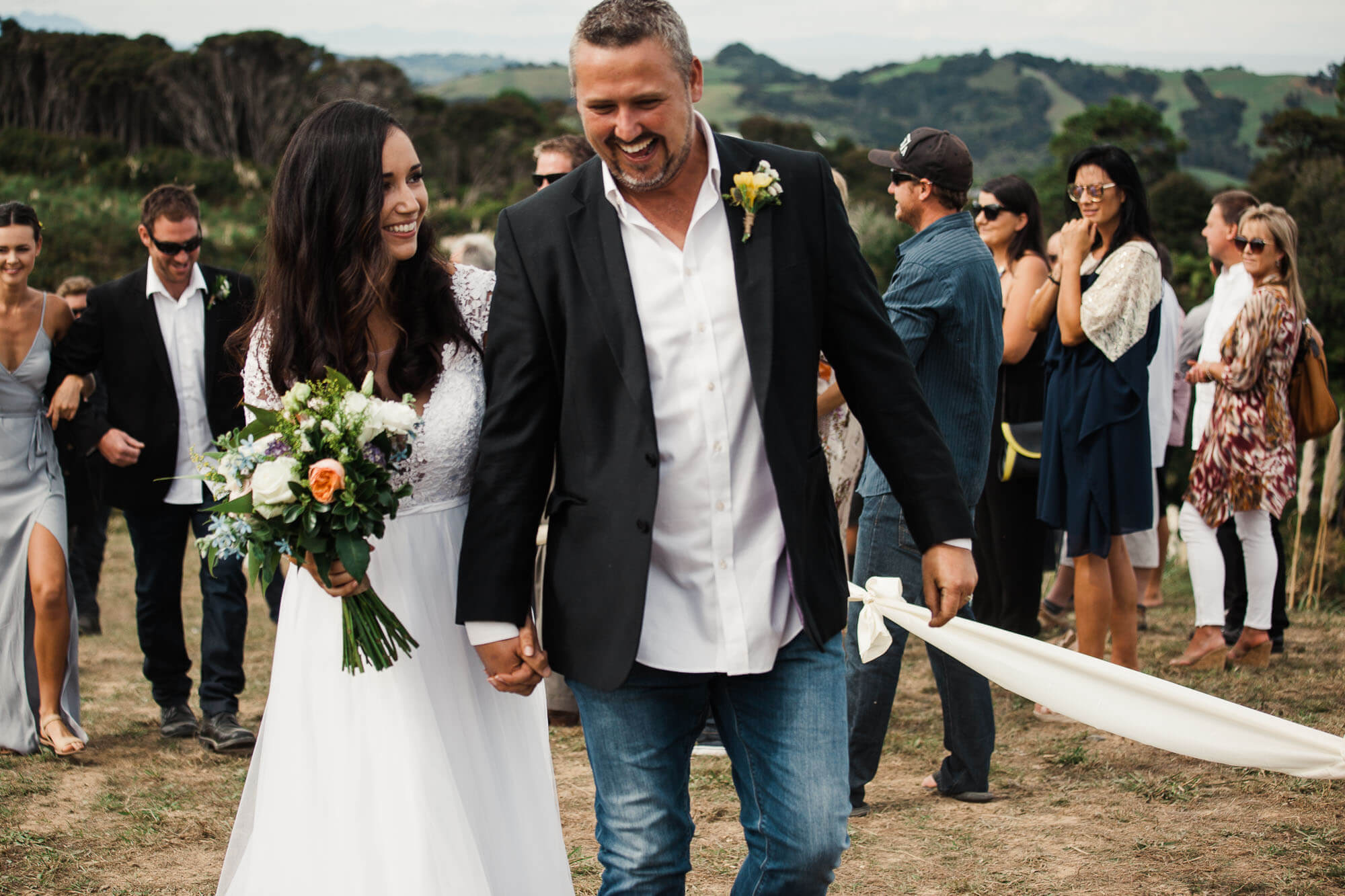 boho-bride-and-groom-walk-down-aisle-at-outdoor-wedding.jpg