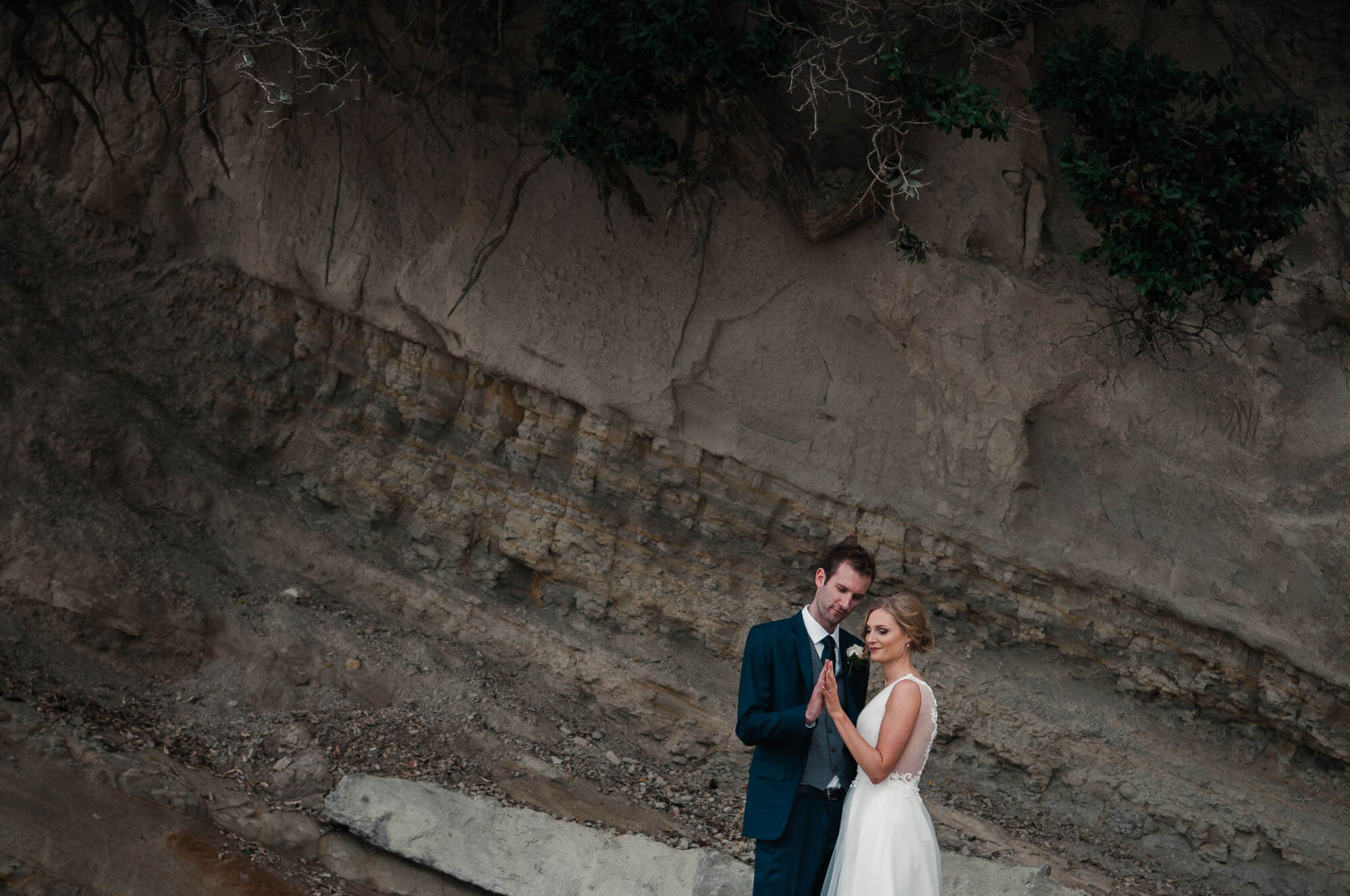 bride-and-groom-holding-hands-with-dramatic-cliff-in-background.jpg
