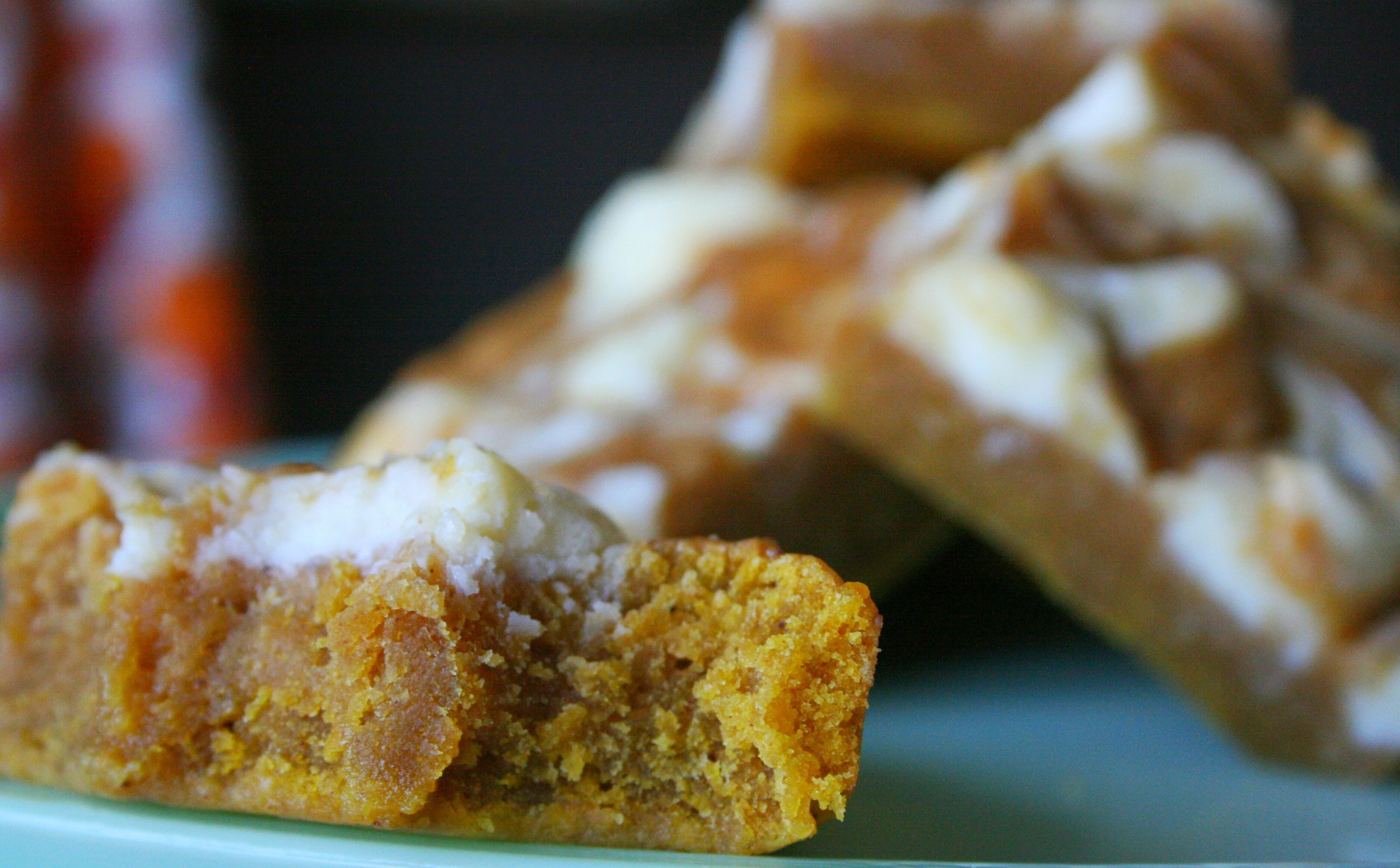 These bars taste the way Autumn feels. The comforting spices of a pumpkin pie married with the creamy tang of a smooth cheesecake with a classic, dense blondie texture.