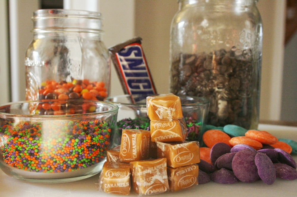 Reeses pieces, snickers, caramels, wilton candy melts and festive sprinkles are the ingredients in this Halloween chocolate bark