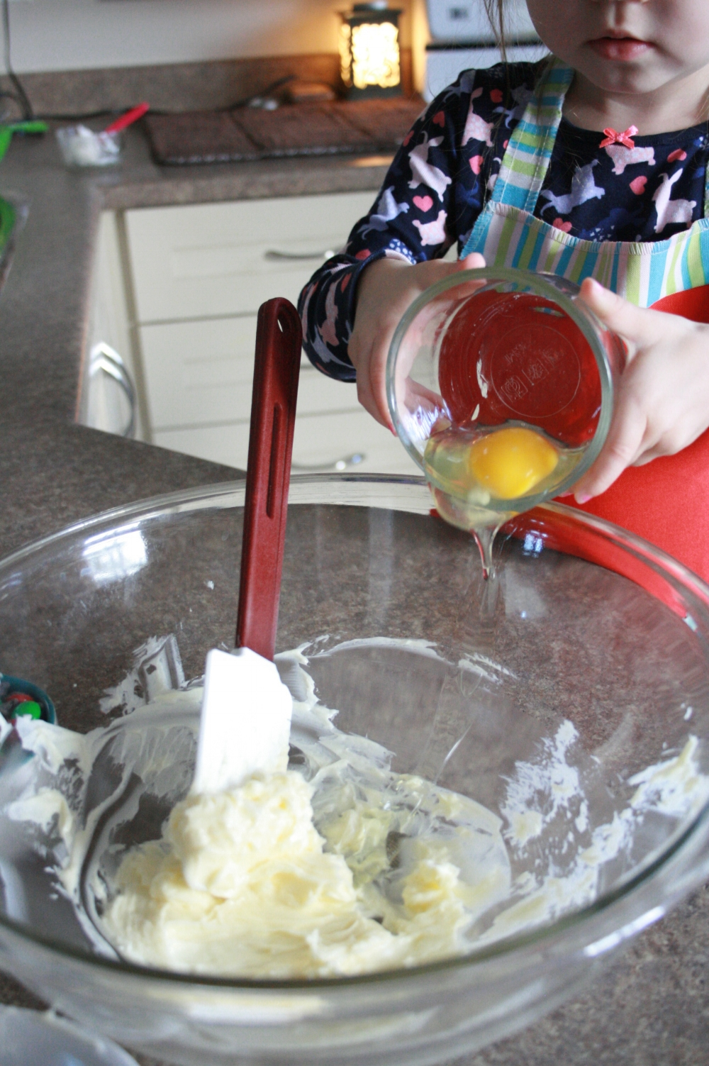 Kid baking cookies, add eggs to softened butter