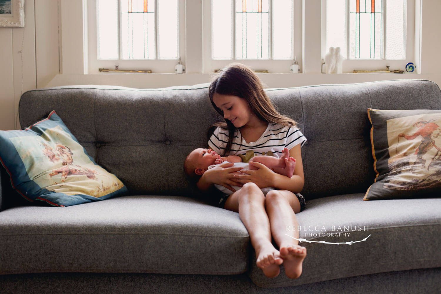 Sister holding her newborn baby brother in a newborn lifestyle photography shoot