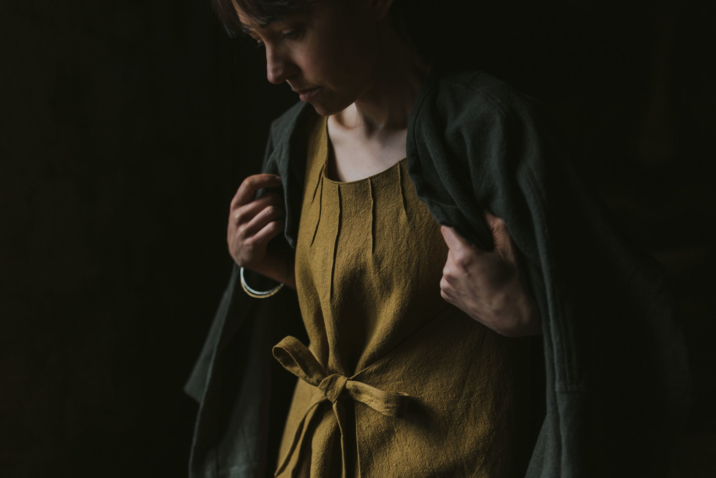 Woman holds collar of jacket over a tunic in a fashion photo shoot.