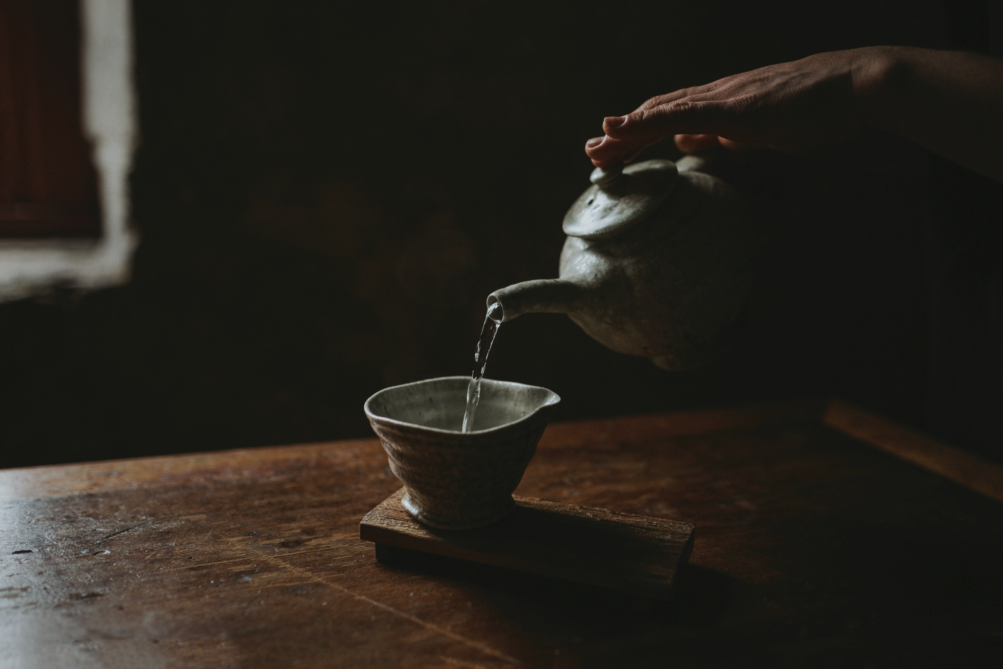 Womans hands pour hot water from a japanese ceramic into a unique artisan tea cup in Hobart.