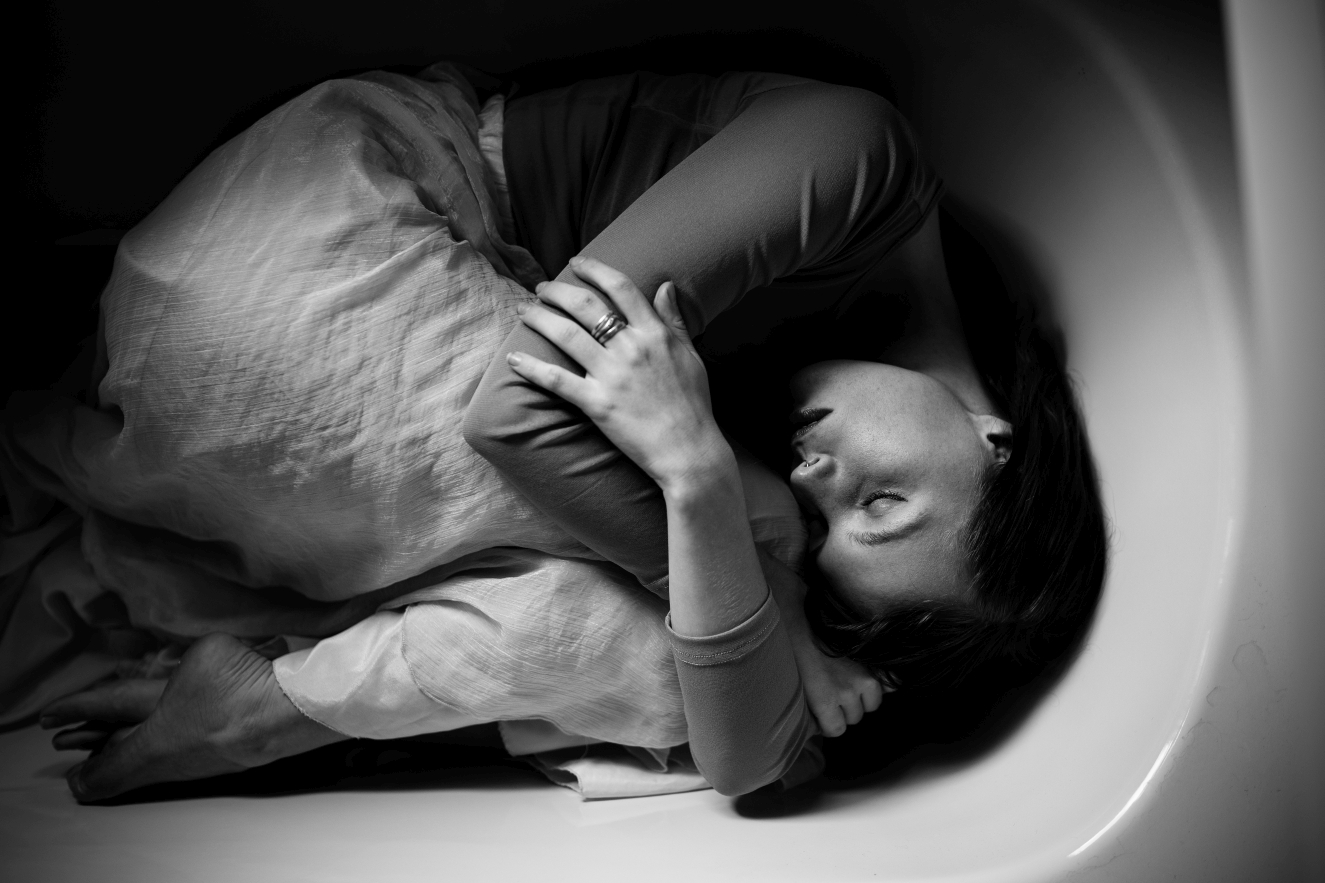 Model-lies-bath-eyes-closed-emotive-siida-photography
