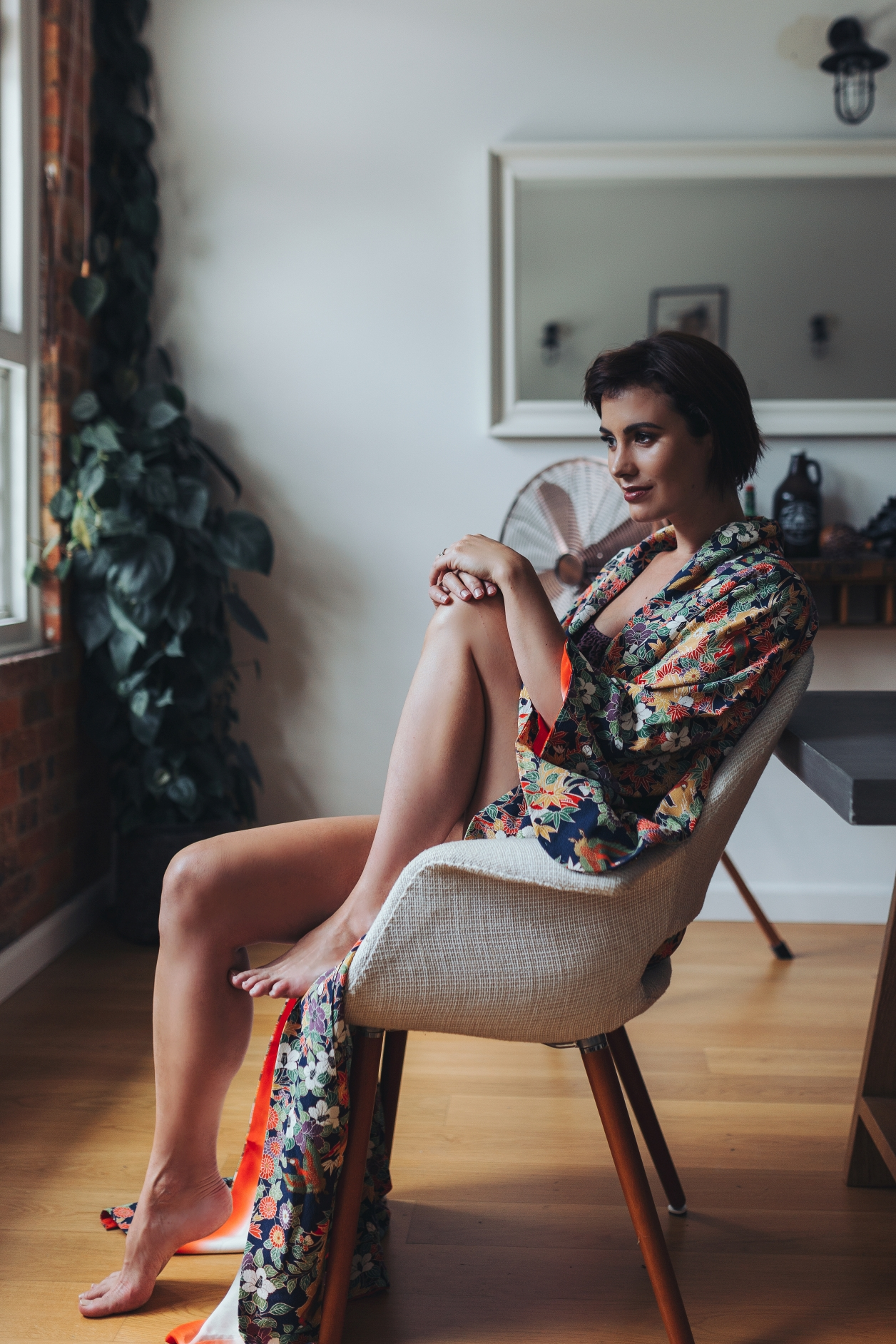 Woman smiles and leans back in chair during fashion photo shoot.