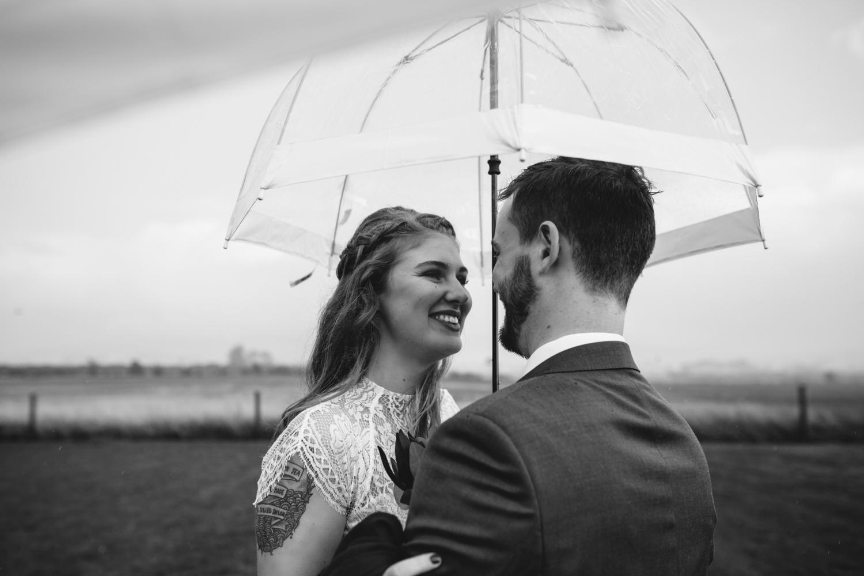 couple shelter under umbrella on their rainy wedding day in Tasmania with siida photography.